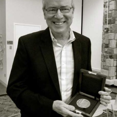 Edwin Romond holds his 2013 New Jersey Poetry Prize medallion at the County College of Morris, Randolph, NJ.